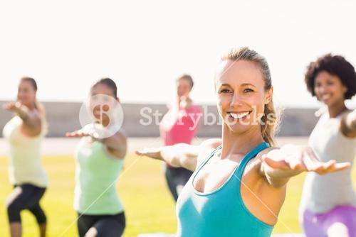 Smiling sporty blonde doing yoga in yoga class