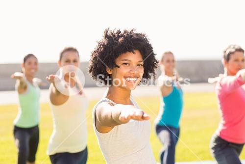 Smiling sporty woman doing yoga in yoga class