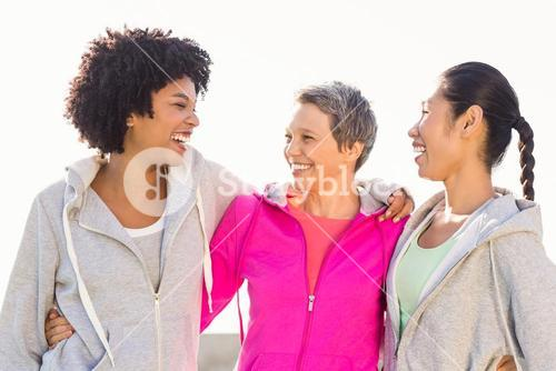 Laughing sporty women with arms around each other