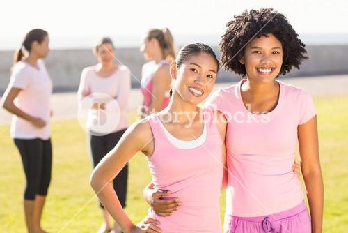 Smiling young women wearing pink for breast cancer