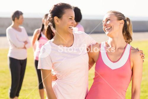 Two smiling women wearing pink for breast cancer