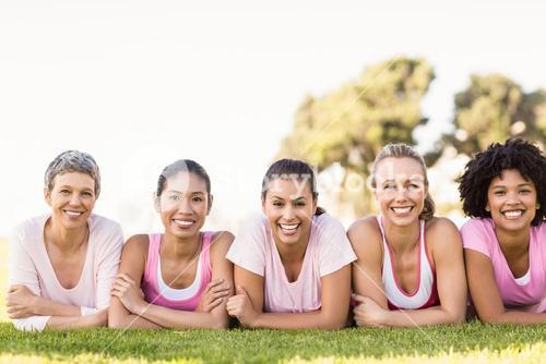 Smiling women lying in a row and wearing pink for breast cancer