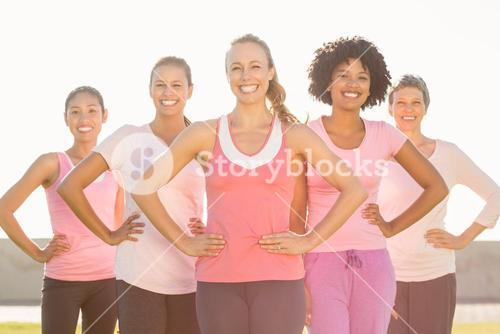 Smiling women wearing pink for breast cancer and posing
