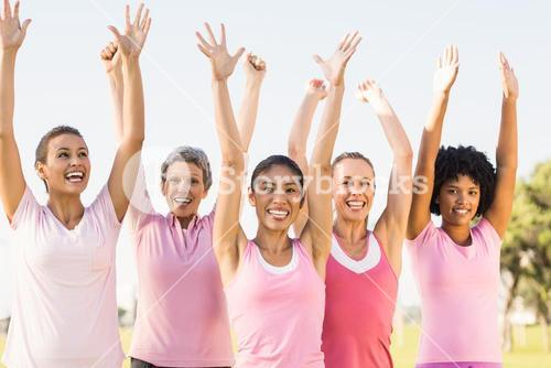 Smiling women wearing pink for breast cancer and cheering