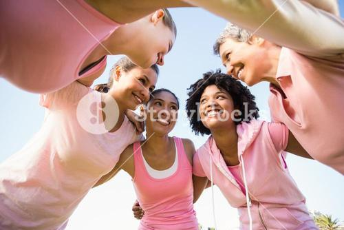 Women wearing pink for breast cancer with arms around