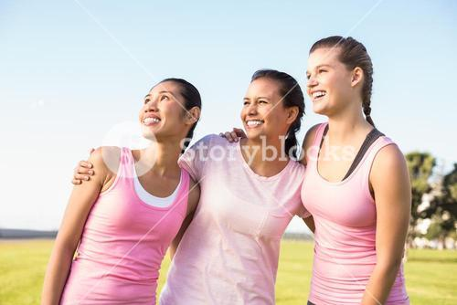Three laughing women wearing pink for breast cancer