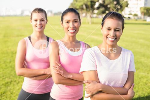 Three smiling women wearing pink for breast cancer