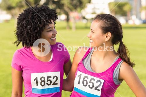 Two smiling runners supporting breast cancer marathon