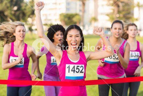 Cheering woman winning breast cancer marathon