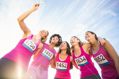 Runners supporting breast cancer marathon and taking selfies