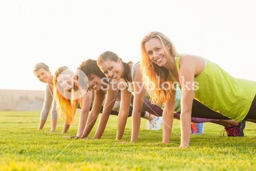 Smiling sporty women doing push ups during fitness class