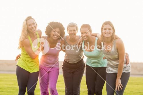 Smiling sporty women with arms around each other