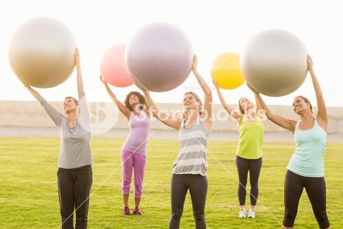 Smiling sporty women working out with exercise balls