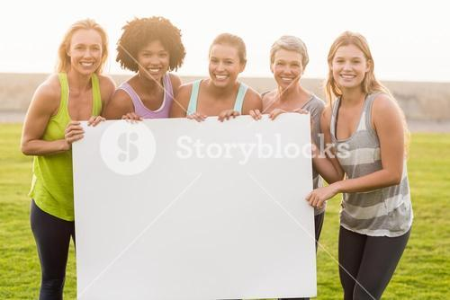 Smiling sporty women holding poster with copy space