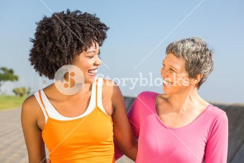 Two sporty women smiling at each other