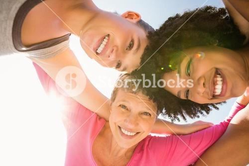 Sporty women with arms around smiling down to camera