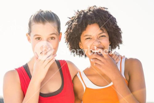 Two young women laughing to camera