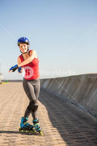 Carefree sporty blonde posing with inline skates