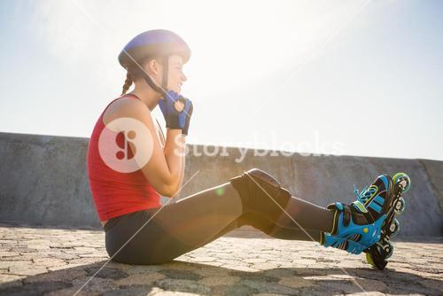 Sporty blonde skater sitting on ground and fastening helmet