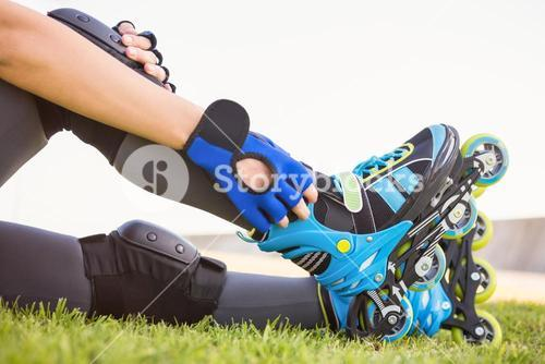 Woman wearing inline skates sitting in grass