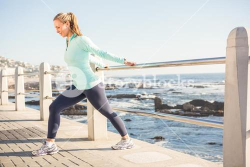 Fit blonde stretching on railing