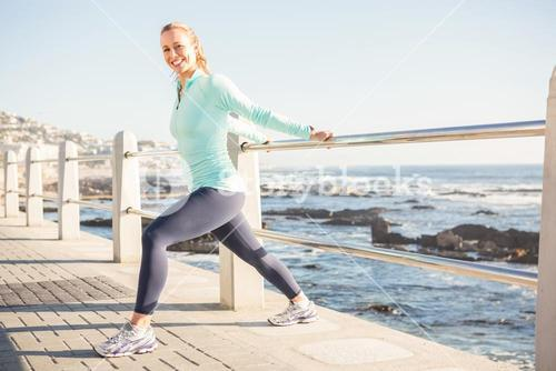 Smiling fit blonde stretching on railing