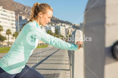 Fit blonde stretching on railing and listening to music