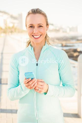 Smiling fit blonde enjoying music and holding phone