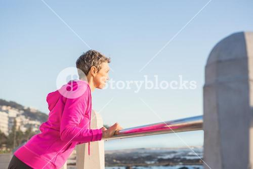 Sporty woman stretching on railing