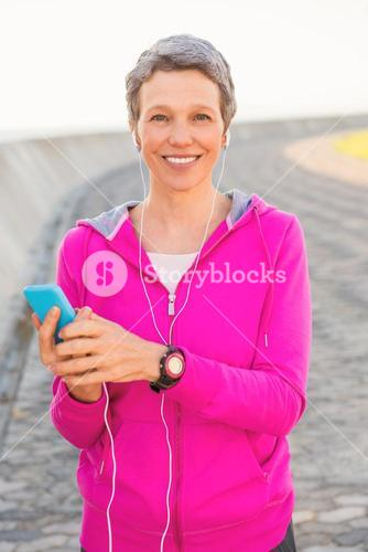 Smiling sporty woman enjoying music and holding phone