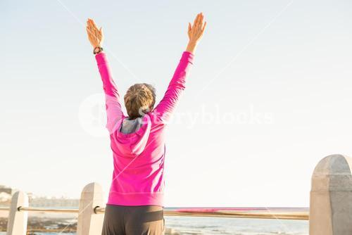 Carefree sporty woman with outstretched arms