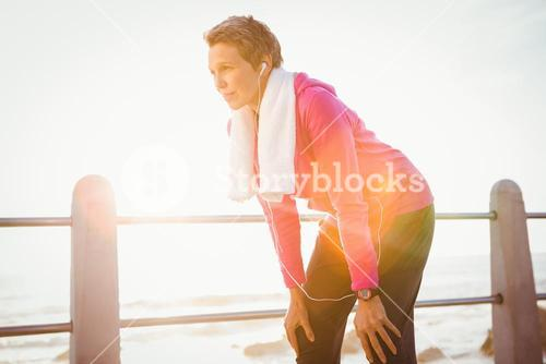 Breathing sporty woman listening to music and resting
