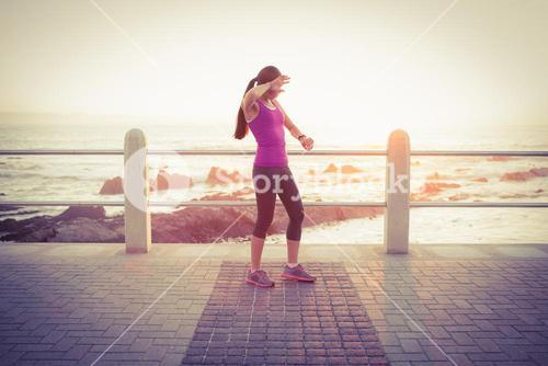 Tired fit woman checking smart watch at promenade