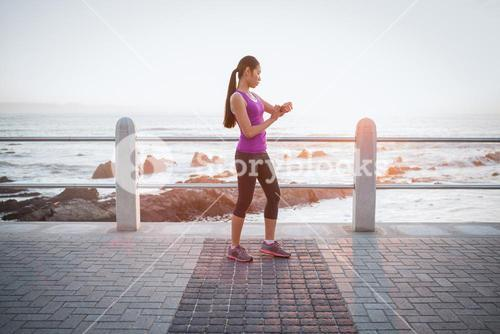 Fit woman checking smart watch at promenade
