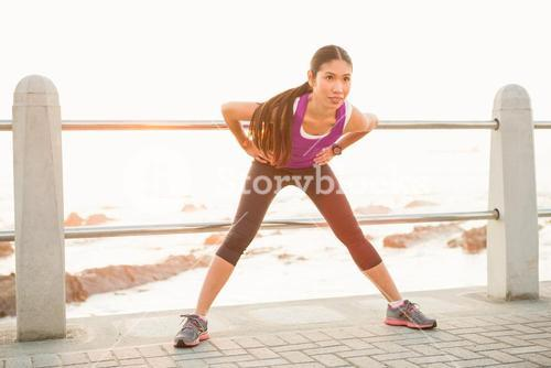 Fit woman stretching at promenade