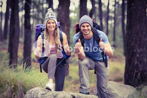Portrait of a happy hiker couple with thumbs up