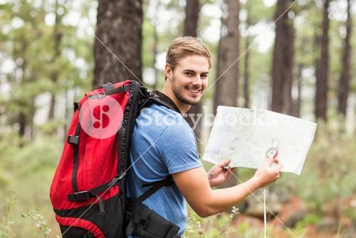 Young handsome hiker using map