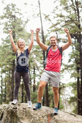 Happy young couple looking at camera with raised hands