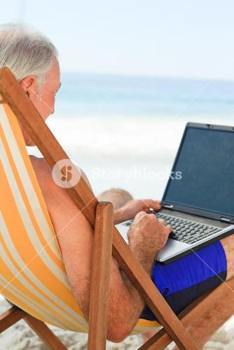 Man working on his laptop at the beach