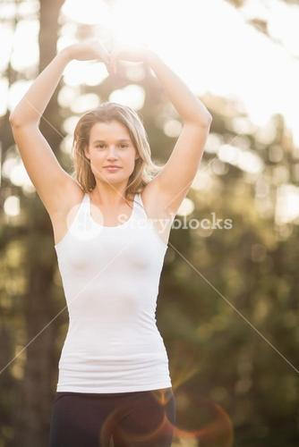 Pretty young jogger shaping heart with arms