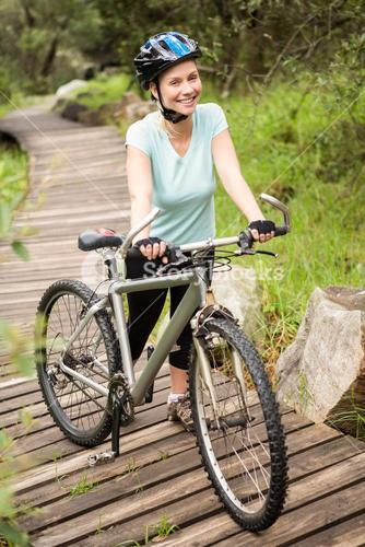 Smiling fit woman rolling her bike