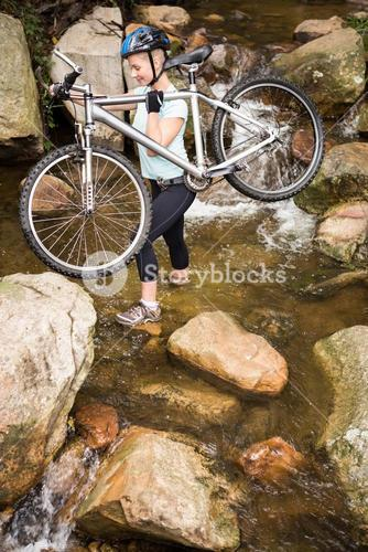 Profile view of a fit woman lifting her bike