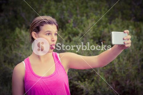 Pretty blonde athlete taking selfies with outstretched tongue