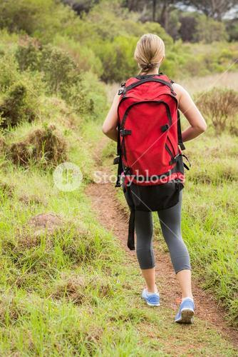 Blonde hiker hiking with backpack