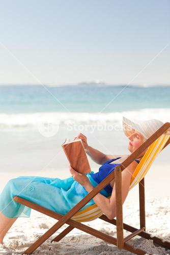 Elderly woman reading a book at the beach