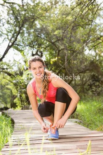 Smiling blonde athlete tying shoelace on wooden trail