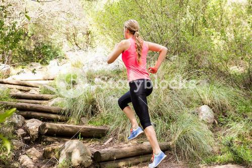 Blonde athlete running up wooden stairs