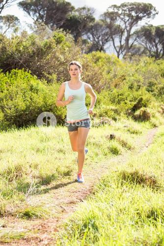 Blonde athlete jogging on trail
