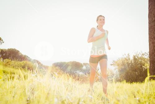 Smiling blonde athlete jogging in grass
