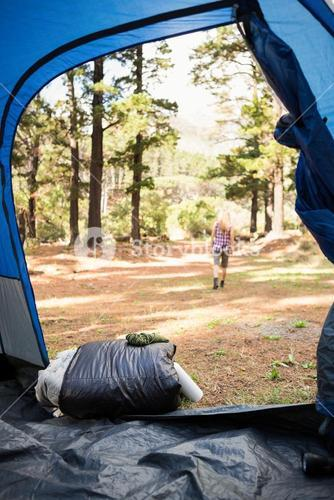 Blonde camper walking away from tent